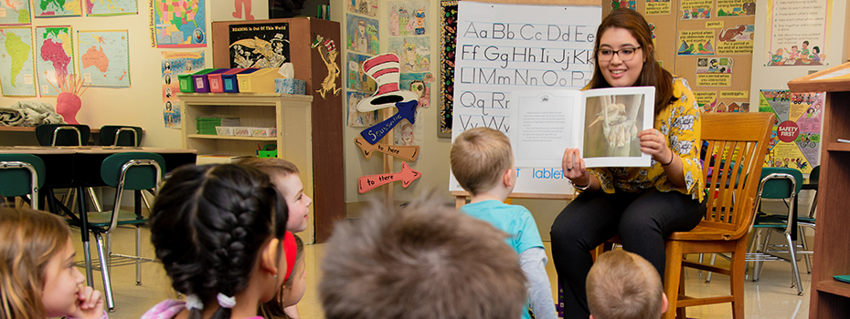 A student teacher reading to elementary students