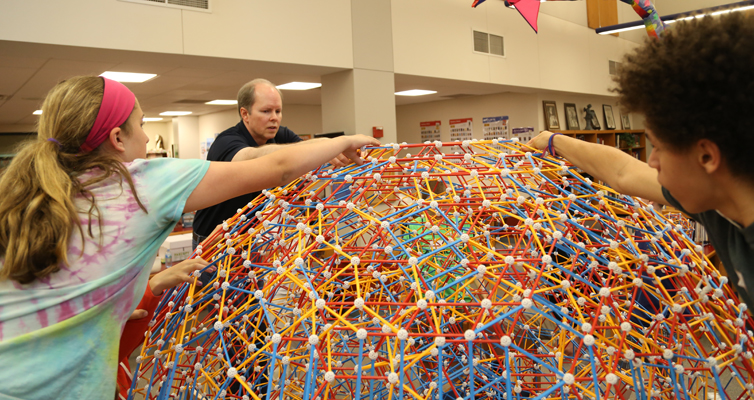 Taylor, Dr. Hill, and Brandon work together to complete the top.