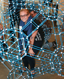 A student crouches in the middle of a large geometric structure.