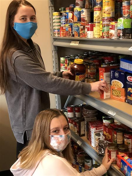 Grace Seeley and Olivia Lattimer stock the Bona Food Pantry