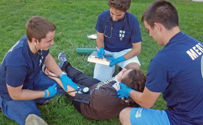 Three Medical Emergency Response Team members assist a fallen student in a training drill