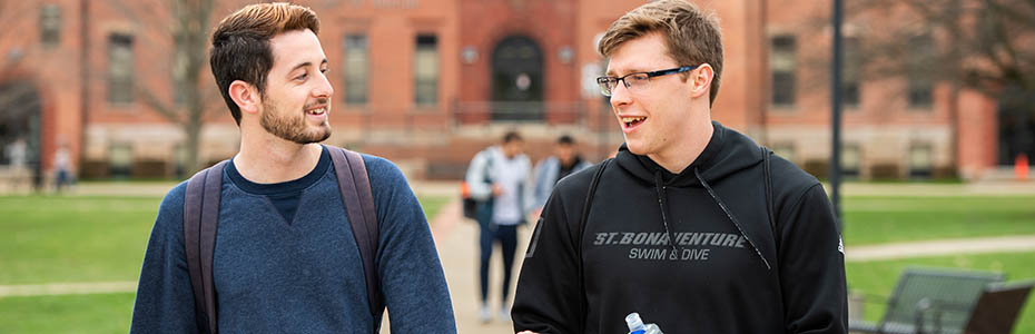 Two male students talking as they walk across campus